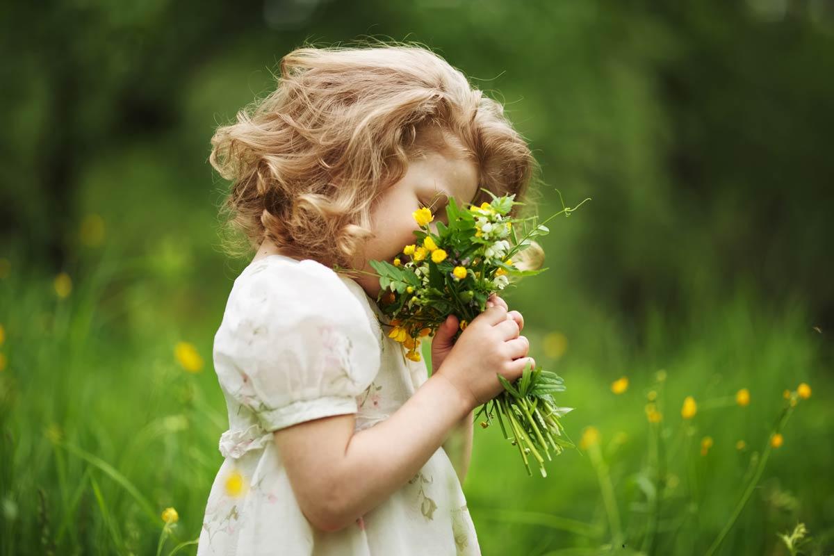Fillette respirant le parfum d'un bouquet de fleurs