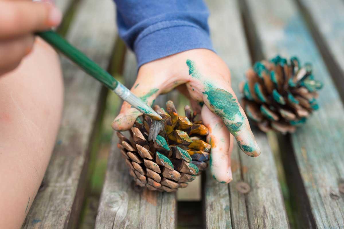 Peinture : enfant et pomme de pin
